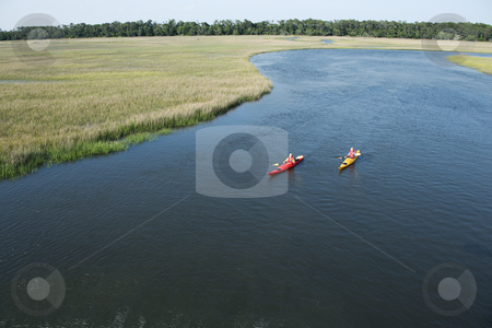 Two boys kayaking. stock photo, Aerial of two teenage boys kayaking through marshland on Bald Head Island, North Carolina. by Iofoto Images