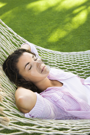 Female in hammock. stock photo, Pretty young adult Caucasian brunette female lying in hammock with arms behind head sleeping. by Iofoto Images