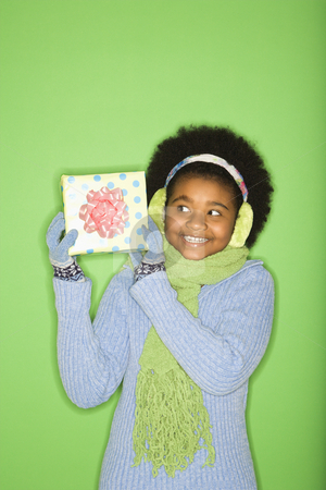 Girl with present. stock photo, African American girl in winter clothing holding wrapped package. by Iofoto Images
