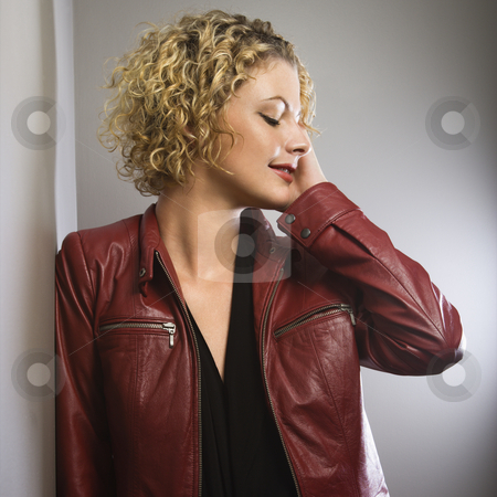 Woman touching face. stock photo, Caucasian young adult woman in red jacket with hand touching face looking away. by Iofoto Images