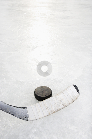Hockey stick and puck. stock photo, Close up of ice hockey stick on ice rink in position to hit hockey puck. by Iofoto Images