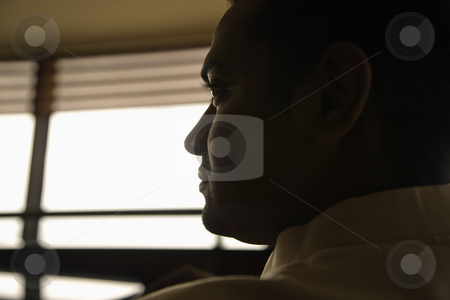 Profile of man. stock photo, Profile view of young adult male Indian slihouetted near window. by Iofoto Images