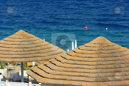 Beach detail stock photo, Straw parasols on a fancy beach against water background by Natalia Macheda