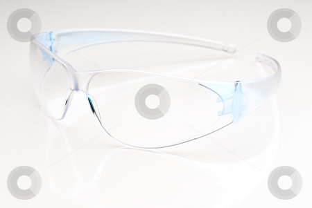 Safety glasses stock photo, Modern safetly glasses on a reflective surface by Vince Clements