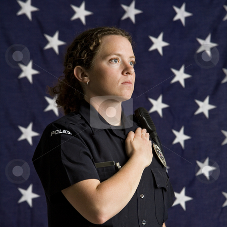 Patriotic policewoman. stock photo, Portrait of mid adult Caucasian policewoman pledging allegiance with American flag as backdrop. by Iofoto Images