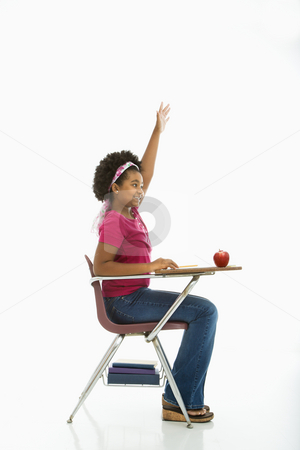 Eager schoolgirl.  stock photo, Side view of African American girl sitting in school desk raising hand. by Iofoto Images