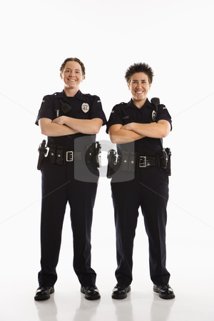 Policewomen crossing arms. stock photo, Portrait of two mid adult Caucasian policewomen standing with arms crossed looking at viewer smiling. by Iofoto Images