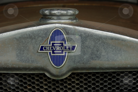 Old Auto Emblem and Radiator Cap stock photo, Close-up of the radiator cap and old emblem marking the grille of a vintage 1930 Chevrolet in a Minnesota sales lot. by Dennis Thomsen