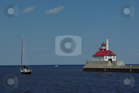 Sailboat Motors by Duluth Lighthouse stock photo, A sailboat motors through the Duluth, Mn harbor canal entry guarded by one of two lighthouses on a sunny, clear, summer day.  The Duluth harbor is the southern entry for shipping on Lake Superior. by Dennis Thomsen