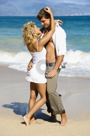 Couple embracing. stock photo, Attractive couple in sensual embrace on Maui, Hawaii beach. by Iofoto Images