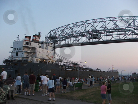 Freighter Arrives at Duluth stock photo, The Argolake a Lake Superior freighter goes through the canal opening to the Duluth Minnesota harbor which requires the lift bridge be raised.  These cargo ships move iron ore (taconite) and other commodities heavy equipment and goods through the Great Lakes waterways. by Dennis Thomsen