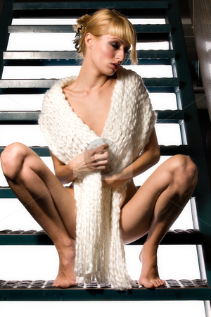 Dressed in only a shawl stock photo, A beautiful blond girl sitting on a pair of stairs wearing only a shawl by Frenk and Danielle Kaufmann