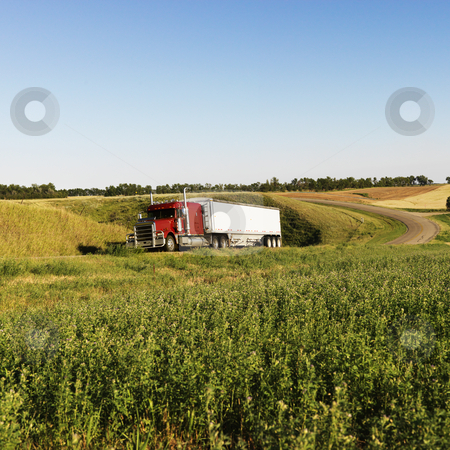 Semi truck on rural road. stock photo, Semi tractor truck on rural road with green plants on shoulder. by Iofoto Images