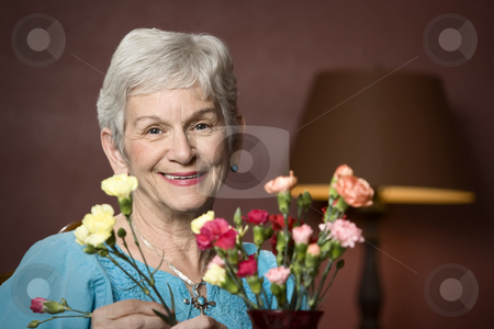 Woman with flowers stock photo, Senior woman at home with colorful flowers by Scott Griessel