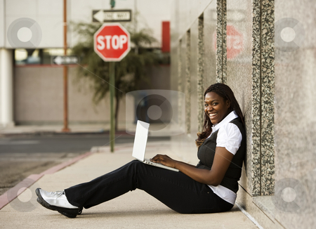 African American Woman with Laptop stock photo, Pretty African American woman on sidealk with laptop computer by Scott Griessel