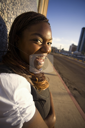 African American Woman Leaning against a Building stock photo, Closeup of a pretty African American woman leaning on a building by Scott Griessel
