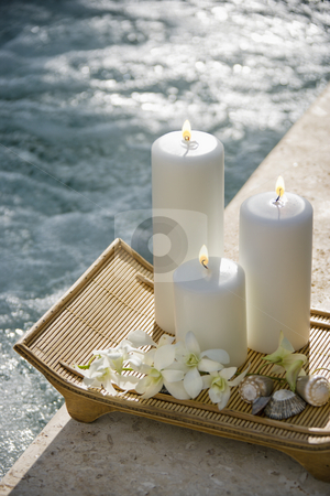 Candles by pool. stock photo, Lit pillar candles on tray with white orchids beside pool. by Iofoto Images
