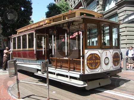 Famous San Francisco Cable Car stock photo, A brakeman turns a Powell Street Cable Car around down near the Embarcadaro. Cable car rides are a San Francisco institution and a popular means of transport tourists and locals up and around the cities hills. San Francisco cable cars are the only moving National Historic Landmark, and 9.7 million people take a ride on these transports each year. Traveling only nine miles per hour, cable cars are powered by electric motors that turn these seemingly endless loops of cable. The motors that run the cables are housed at the Cable Car Barn Museum, in San Francisco. by Dennis Thomsen