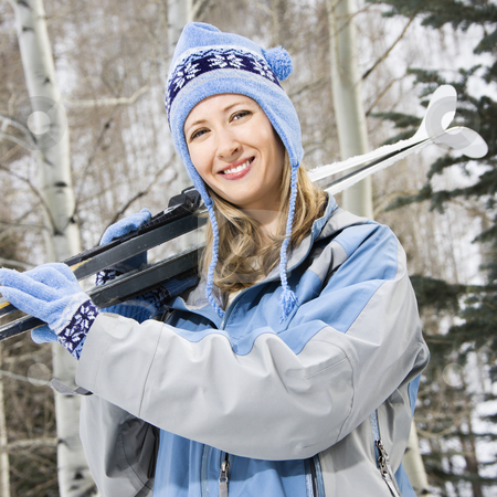 Female holding skis. stock photo, Mid adult Caucasian female skier wearing blue ski clothing carrying skis on shoulder. by Iofoto Images