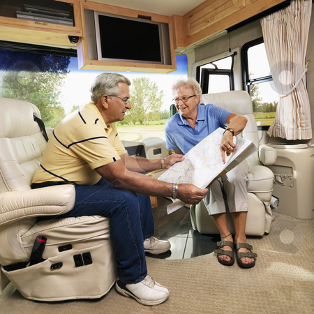 Senior couple in RV. stock photo, Senior couple sitting in RV looking at map and smiling. by Iofoto Images