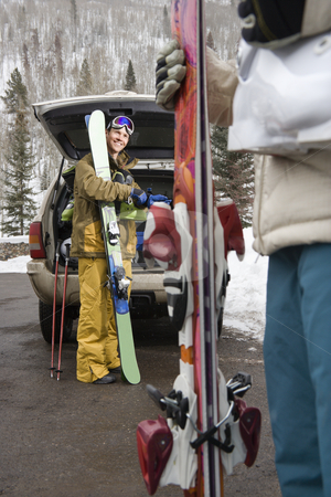 Couple going skiing. stock photo, Couple standing with ski equipment by open vehicle smiling. by Iofoto Images
