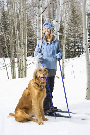 Woman and dog. stock photo, Mid adult smiling Caucasian female skier wearing blue ski clothing standing on ski slope with Golden Retriever. by Iofoto Images