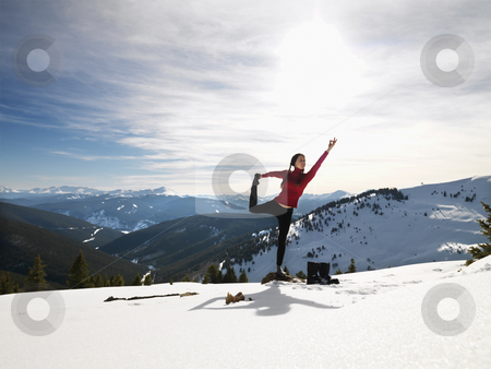 Woman doing yoga in snow. stock photo, Young woman doing yoga pose on rock in snow in mountainous terrain. by Iofoto Images