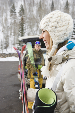 Couple on vacation. stock photo, Couple standing with ski equipment by open vehicle smiling and laughing. by Iofoto Images