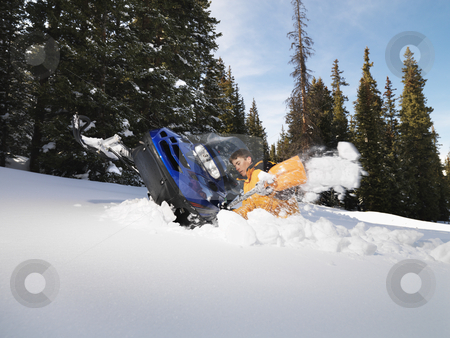 Man with stuck snowmobile. stock photo, Young man digging out snowmobile submerged in the snow. by Iofoto Images