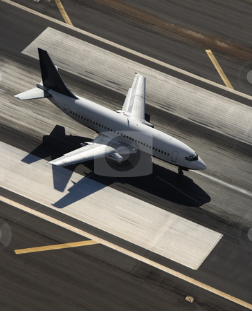 Airplane on runway. stock photo, Aerial view of passenger airplane on airport runway. by Iofoto Images