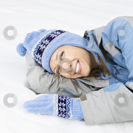 Woman in snow. stock photo, Attractive smiling mid adult Caucasian woman wearing blue ski clothing lying in snow looking at viewer. by Iofoto Images