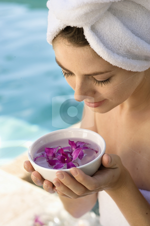 Woman at spa. stock photo, Caucasian mid-adult woman wearing towel around head and body holding bowl of purple orchids next to pool. by Iofoto Images