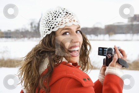 Woman using video camera. stock photo, Smiling Caucasian young adult female in winter clothing holding video camera and looking over shoulder at viewer. by Iofoto Images