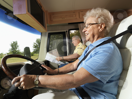 Senior woman driving RV. stock photo, Senior adult woman driving RV and smiling while man reads map in passenger seat. by Iofoto Images