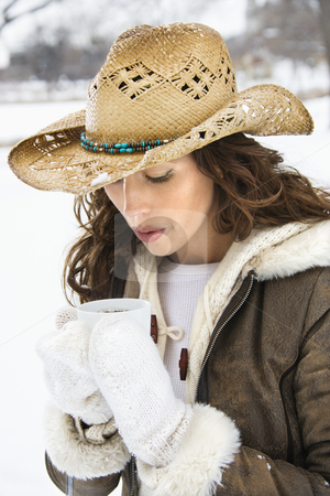 Woman blowing on coffee. stock photo, Caucasian young adult female outdoors in snow blowing into coffee cup and wearing straw cowboy hat. by Iofoto Images