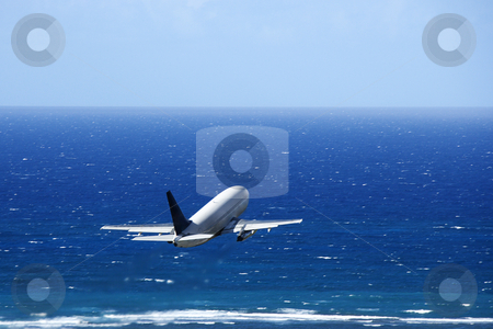 Airplane over ocean. stock photo, Passenger airplane taking off from airport headed over the Pacific ocean. by Iofoto Images