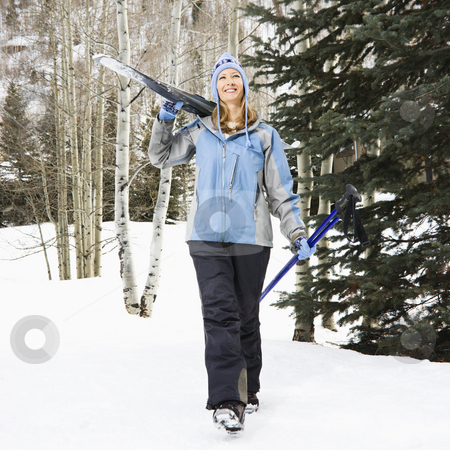 Female skier on slope. stock photo, Mid adult Caucasian female skier wearing blue ski clothing walking and carrying skis on shoulder. by Iofoto Images