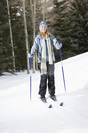 Female skier. stock photo, Mid adult Caucasian female skier wearing blue ski clothing standing on ski slope smiling. by Iofoto Images