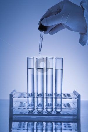 Hand holding dropper. stock photo, Hand holding dropper over test tubes. by Iofoto Images
