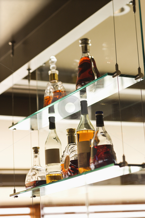 Liquor bottles. stock photo, Glass shelves with liquor bottles. by Iofoto Images