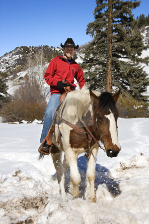 Man horseback riding in snow. stock photo, Young Caucasian man horseback riding in snowy mountains looking at viewer. by Iofoto Images