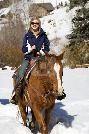 Woman horseback riding in snow. stock photo, Young Caucasian woman horseback riding in snow and smiling at viewer. by Iofoto Images