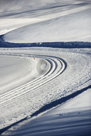 Vehicle tracks in snow. stock photo, Snowmobile tracks winding through winter snow. by Iofoto Images
