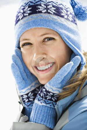 Attractive smiling woman. stock photo, Portrait of attractive smiling mid adult Caucasian woman wearing blue ski cap and gloves looking at viewer. by Iofoto Images