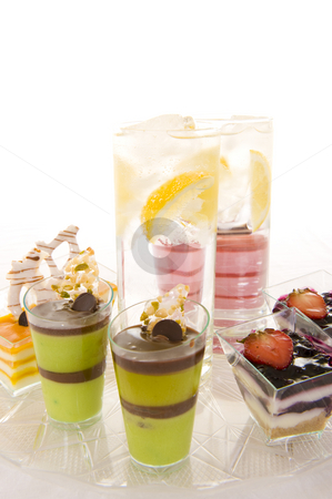 Sparkling water and confectionery stock photo, Glasses with sparkling water containing fresh lemon slices, surrounded by colorful confectionery on a white background. by Nicolaas Traut