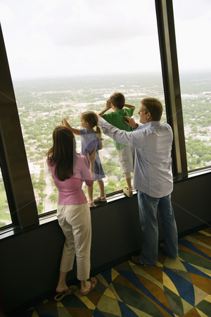 Family at window. stock photo, Caucasian family looking out observation deck at Tower of the Americas in San Antonio, Texas. by Iofoto Images