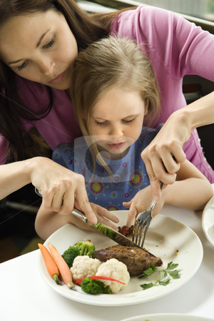 Mom helping daughter cut food. stock photo, Caucasian mother helping cut meat for her daughter. by Iofoto Images