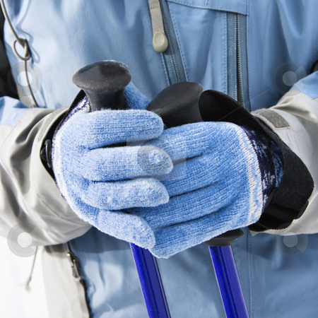 Ski gloves and poles. stock photo, Close up of female skier hands wearing blue gloves holding ski poles. by Iofoto Images