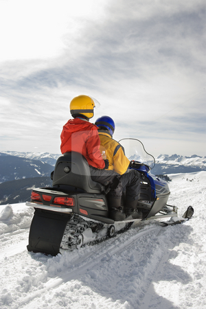 Couple on snowmobile. stock photo, Man and woman riding on snowmobile in snowy mountainous terrain. by Iofoto Images