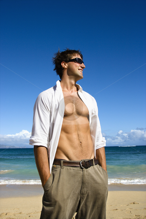 Attractive man. stock photo, Portrait of attractive man standing with shirt unbuttoned wearing sunglasses on Maui, Hawaii beach. by Iofoto Images